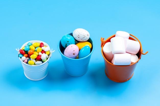 Une vue de face des bonbons et des guimauves sucrées savoureuses à l'intérieur de petites trempettes