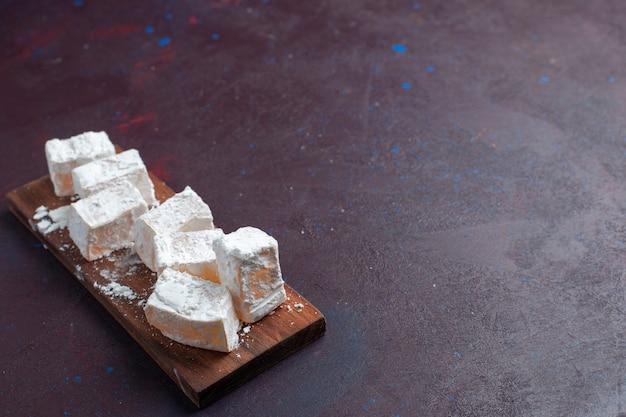 Vue de face de bonbons en poudre de sucre délicieux nougat sur la surface sombre