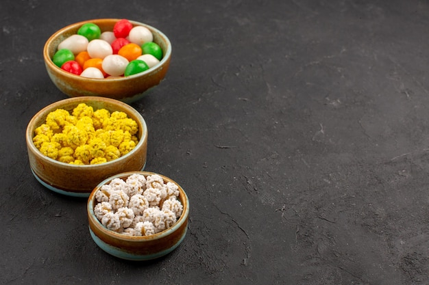 Vue de face des bonbons sucrés colorés sur un espace sombre