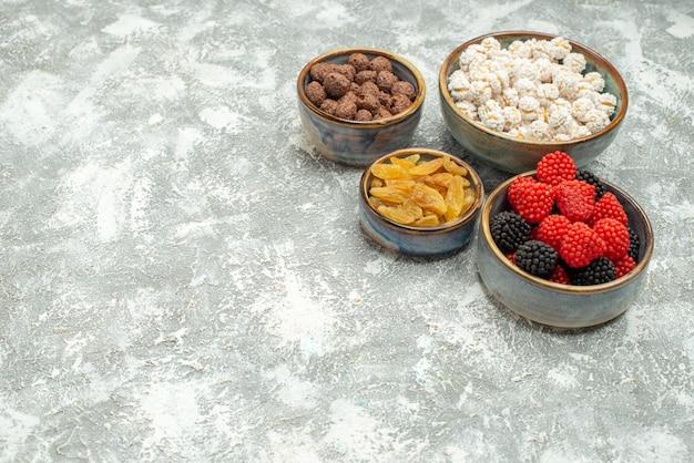 Vue de face des bonbons sucrés avec des confitures sur un espace blanc