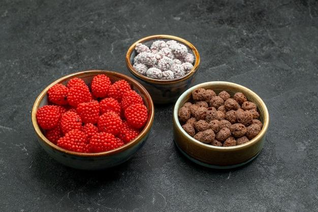 Vue de face de bonbons sucrés à l'intérieur de petits pots sur l'espace gris