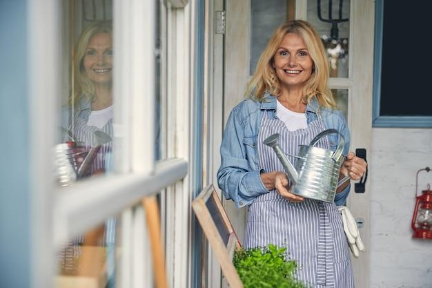Vue de face d'une botaniste souriante tenant un arrosoir galvanisé à deux mains