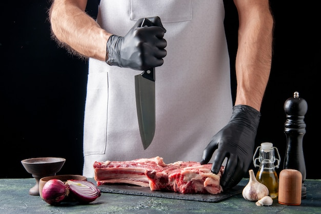 Vue de face boucher mâle coupant la viande sur une surface sombre