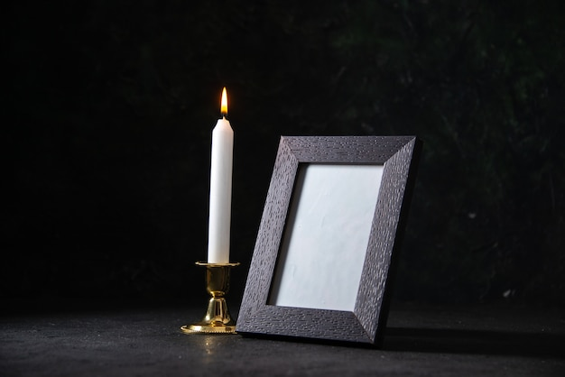 Vue de face d'une bougie blanche avec cadre photo sur dark