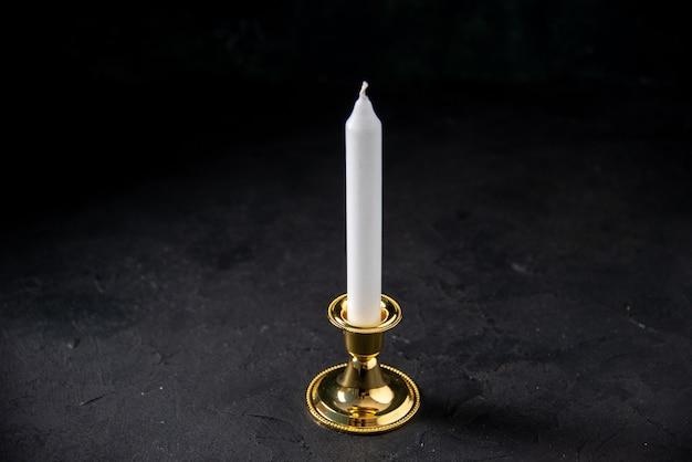 Vue de face d'une bougie blanche dans un insert doré sur le noir