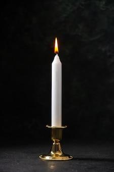 Vue de face de la bougie blanche en support doré sur le noir