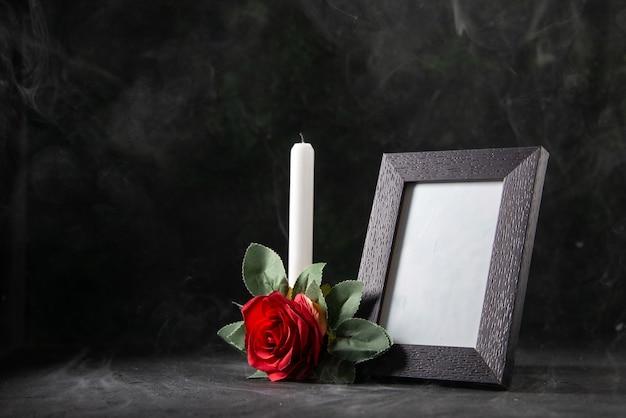 Vue de face de la bougie sans feu avec cadre photo sur fond noir
