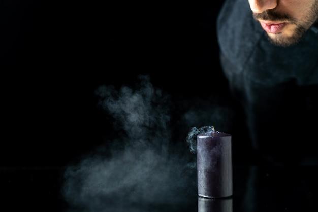 Vue de face de la bougie sombre devient sans fil par l'homme sur une surface sombre
