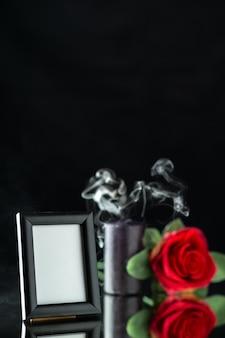 Vue de face de la bougie sombre avec rose rouge et cadre photo sur une surface sombre