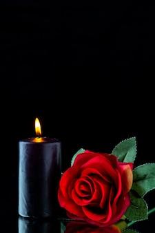 Vue de face de la bougie sombre avec rose rouge sur la surface sombre