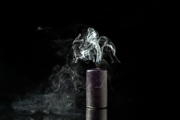 Vue de face de la bougie sombre sans feu sur une surface sombre