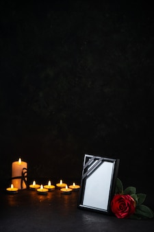 Vue de face des bougies allumées avec cadre photo sur une surface sombre