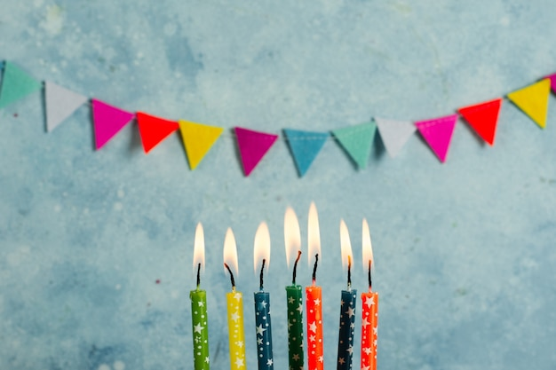 Vue de face de bougies allumées multicolores avec guirlande