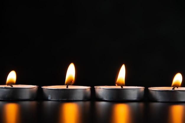 Vue de face des bougies allumées sur une surface sombre