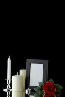 Vue de face de bougies blanches avec cadre photo et fleur rouge sur mur noir