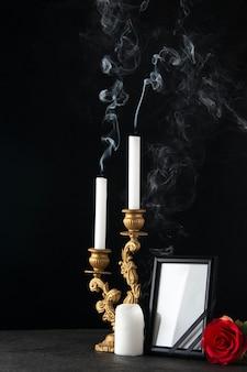 Vue de face des bougies sans feu avec cadre photo sur fond noir
