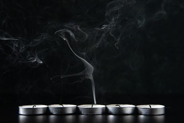 Vue de face des bougies sans feu sur fond noir