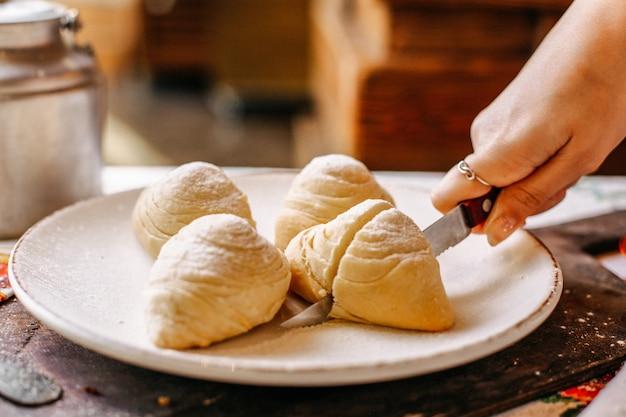 Une vue de face de la boulangerie orientale de badambura avec des noix douces à l'intérieur se trancher à l'intérieur de la pâte à biscuits plaque blanche