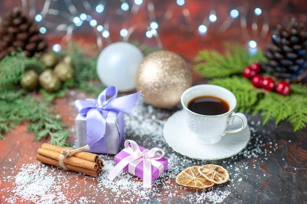 Vue de face boules d'arbre de noël tasse de thé petits cadeaux poudre de noix de coco sur fond sombre isolé