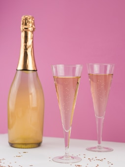 Vue de face de la bouteille de champagne avec des verres remplis
