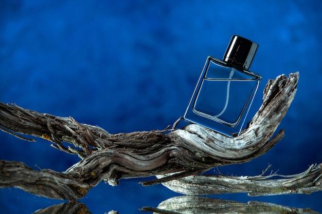 Vue de face d'une bouteille d'eau de cologne sur une branche d'arbre pourrie sur fond bleu foncé avec espace libre