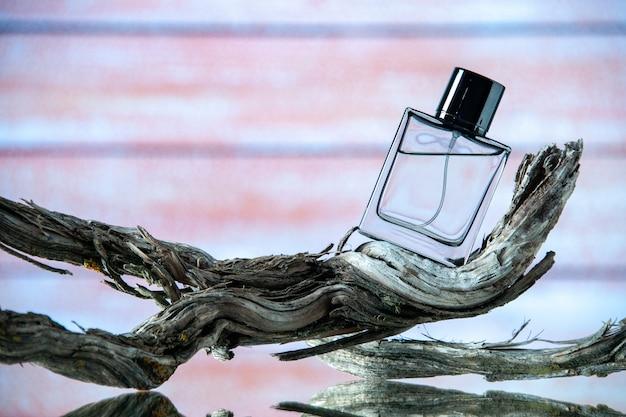 Vue de face de la bouteille d'eau de cologne sur une branche d'arbre pourrie sur fond de bois beige