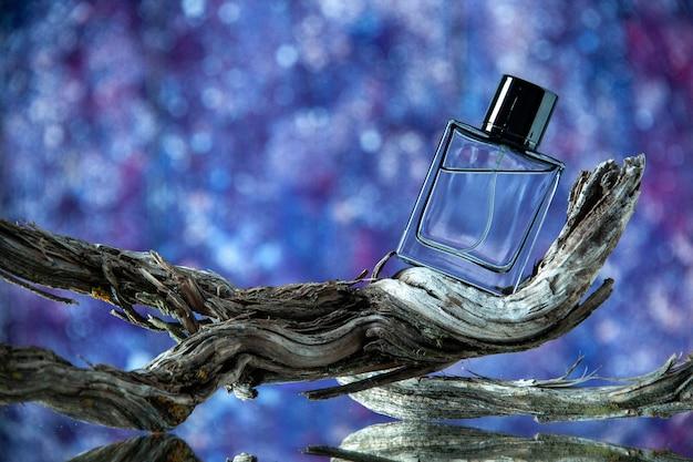 Vue de face de la bouteille d'eau de cologne sur une branche d'arbre pourrie isolée sur fond violet flou