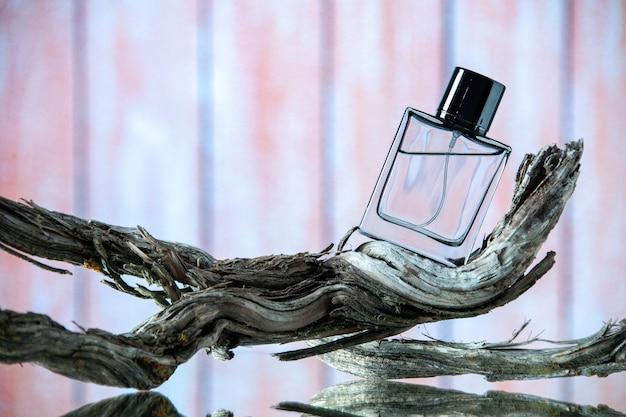 Vue de face d'une bouteille d'eau de cologne rectangle sur une branche d'arbre pourrie sur du bois beige