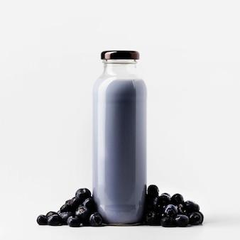 Vue de face de la bouteille de jus de myrtille avec des fruits