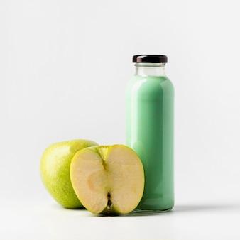 Vue de face de la bouteille de jus de pomme avec des fruits