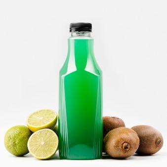 Vue de face de la bouteille de jus vert avec limes et kiwi