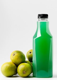 Vue de face de la bouteille de jus vert avec limes