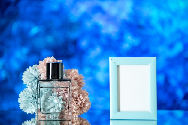 Vue de face bouteille de parfum bleu cadre photo fleurs sur fond bleu clair