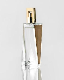 Une vue de face une bouteille de parfum conçue en brun argenté sur le bureau blanc