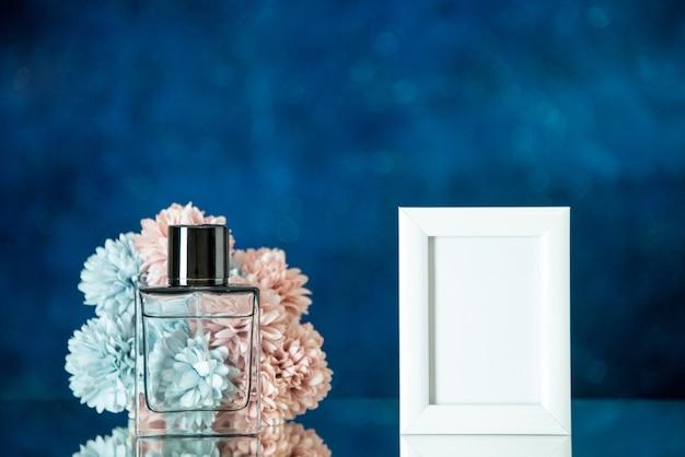 Vue de face bouteille de parfum petit cadre photo blanc fleurs sur fond bleu foncé