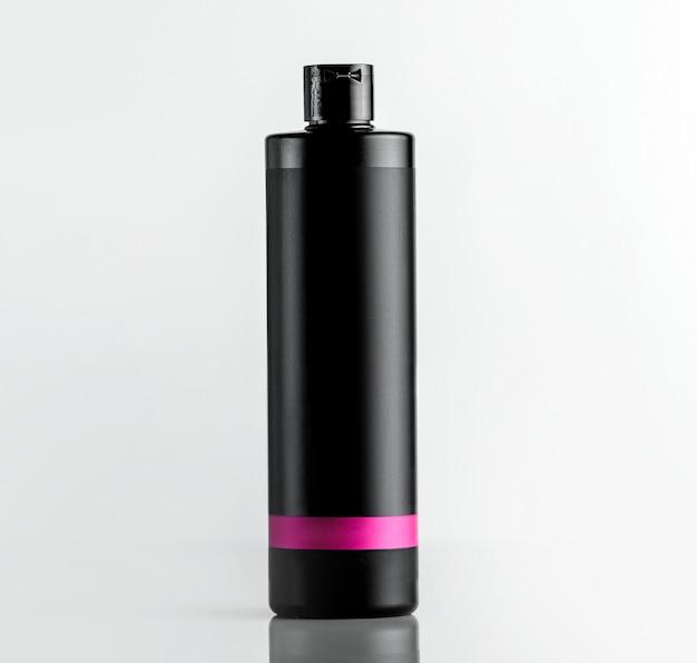 Vue de face bouteille en plastique noir sous shampooing avec une bande rose