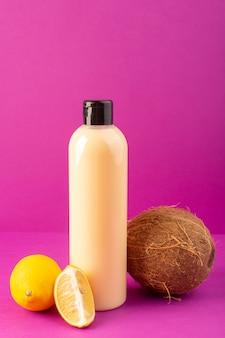 Une vue de face bouteille de shampooing en plastique de couleur crème peut avec capuchon noir avec des citrons et de la noix de coco isolé sur le fond violet cheveux beauté