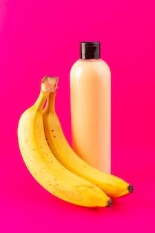 Une vue de face bouteille de shampooing en plastique de couleur crème peut avec capuchon noir isolé avec des bananes sur les cheveux de beauté cosmétiques fond rose