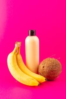 Une vue de face bouteille de shampooing en plastique de couleur crème peut avec capuchon noir isolé avec des bananes et de la noix de coco sur les cheveux de beauté cosmétiques fond rose