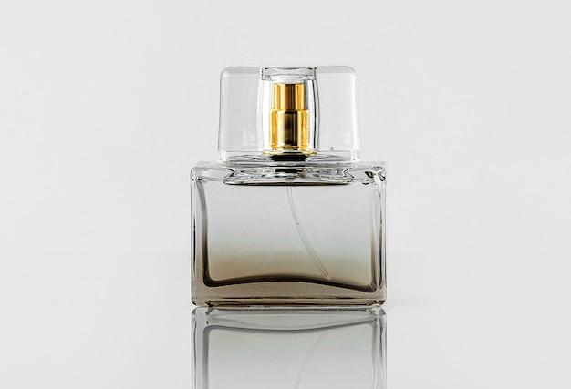 Une vue de face bouteille transparente parfum isolé sur le mur blanc