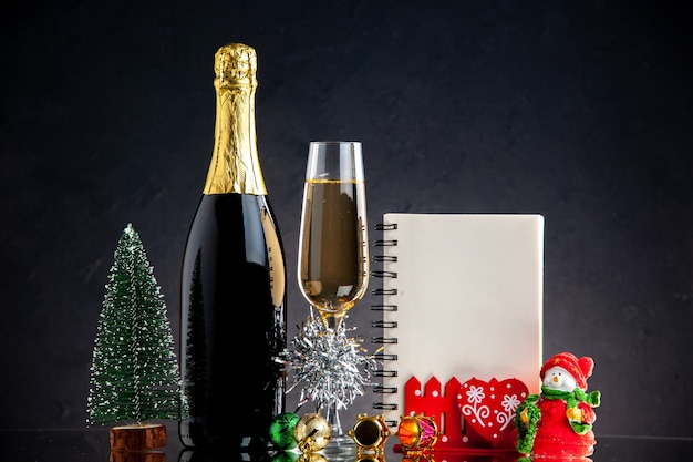 Vue de face bouteille de verre de champagne ornements de noël cahier mini arbre de noël sur une surface sombre