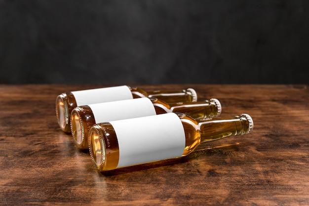 Vue de face des bouteilles de bière horizontales avec des étiquettes vierges