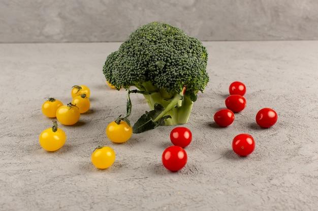 Vue de face brocoli vert frais mûr avec des tomates jaunes et rouges sur le gris
