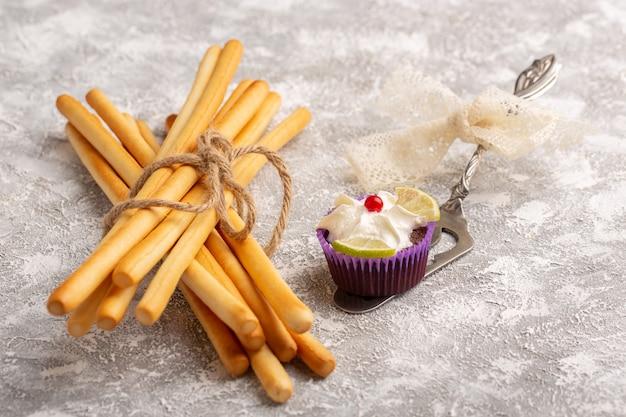 Vue de face des brownies au chocolat avec de la crème et des tranches de citron avec des craquelins en bâton