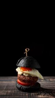 Vue de face burger noir avec oeuf et copie-espace