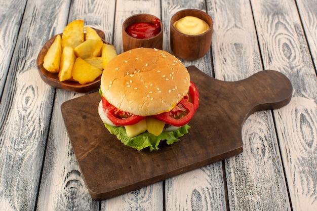 Une vue de face burger de viande avec du fromage et des pommes de terre à salade verte et trempettes sur la table en bois et table grise de la nourriture