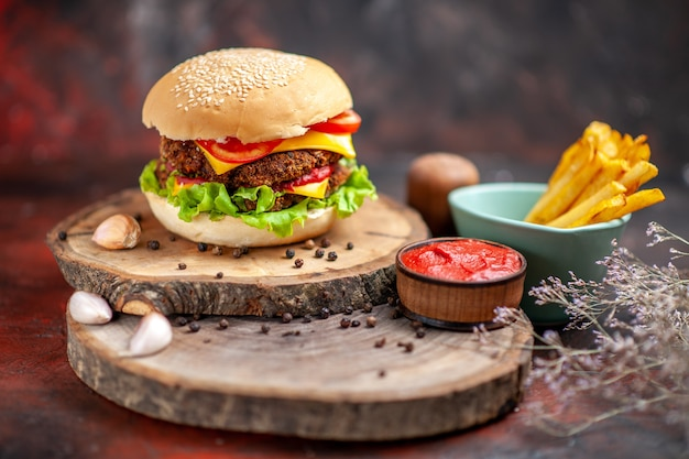Vue de face burger de viande avec des frites sur le fond sombre
