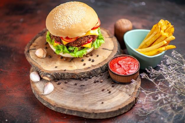 Vue de face burger de viande avec fromage tomates et salade sur fond sombre