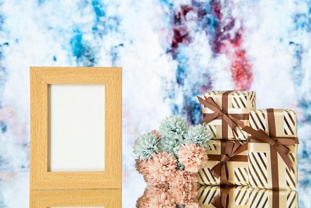 Vue de face cadeaux de mariage cadre photo vierge fleurs