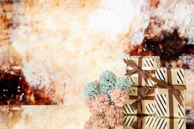Vue de face des cadeaux de mariage et des fleurs reflétées sur le miroir
